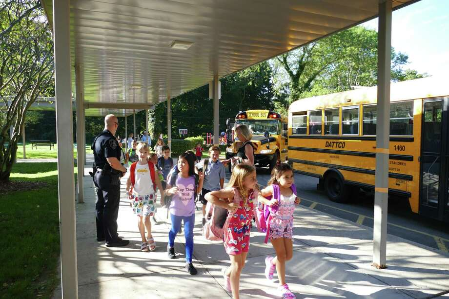 Children get off the bus at West school in New Canaan on a recent first day of school. Photo: Grace Duffield / Hearst Connecticut Media