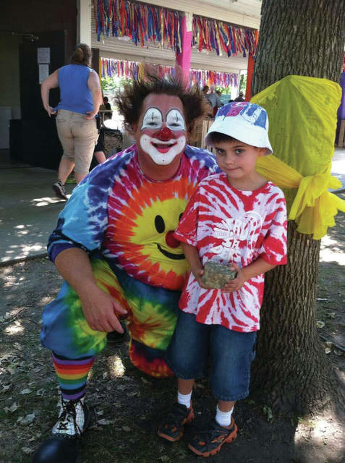 Dooley the Clown poses with a child at the Midwest Salute to the Arts festival, where he will be this year all day, both Saturday, Aug. 24 & Sunday, Aug. 25.