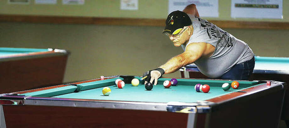 A patron lines up his shot on a pool table at Riverbend Billiards in Alton, which will close at the end of August after 30 years in business.