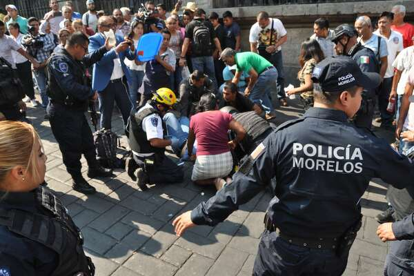 An injured man receives first aid after a gunman opened fire in the central square of Cuernavaca, Morelos state, in Mexico on May 8, 2019. - Two leaders of the Confederation of Mexican Workers (CTM), Mexico's largest labor union confederation, were killed in the attack, and other two people were wounded. (Photo by str / AFP) (Photo credit should read STR/AFP/Getty Images)