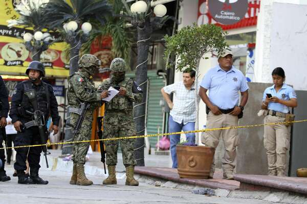Soldiers from the National Guard, State Police officers of Guerrero and Municipal Police officers of Acapulco guard an area where gunmen killed and wounded multiple people inside a bar in Acapulco, Mexico, Sunday July 21, 2019. (AP Photo/Bernardino Hernandez)