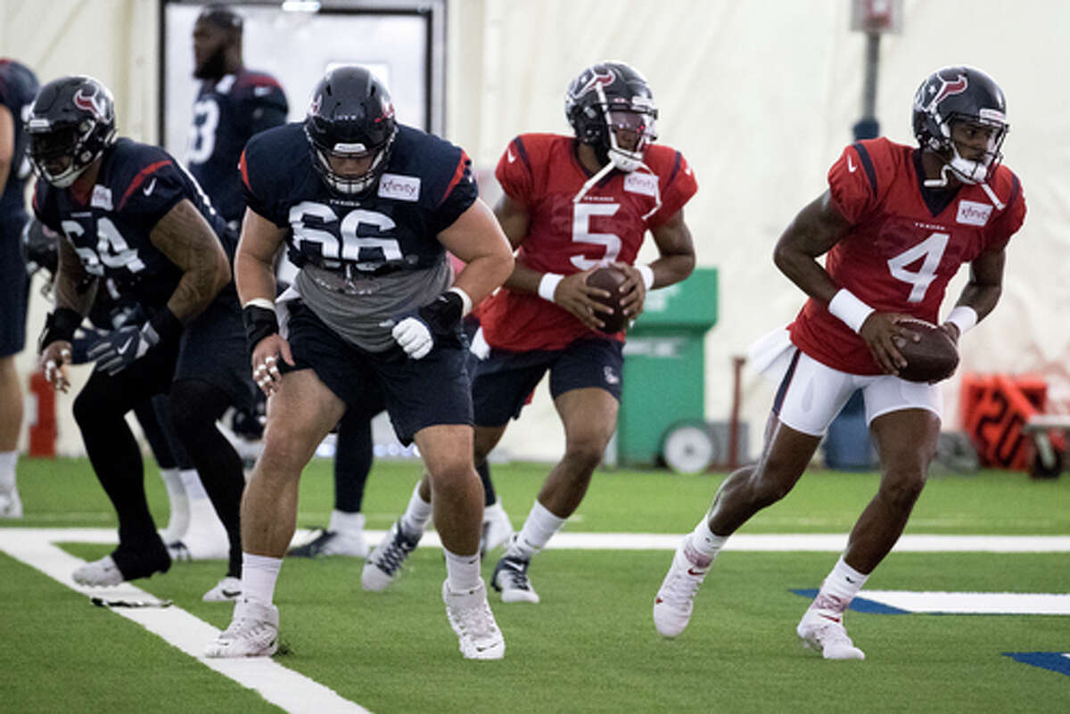 Houston Texans quarterback Deshaun Watson (4) takes a snap from center Nick Martin (66) during training camp at the Methodist Training Center on Wednesday, Aug. 21, 2019, in Houston.
