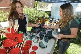 Tara White, from Trumbull, buys a few peices and some ceramic bowls from Krista Verbitsky, who hand makes them in her Trumbull pottery studio, This Girl Does That, during the 2018 Trumbull Arts Festival. The event returns September 15.
