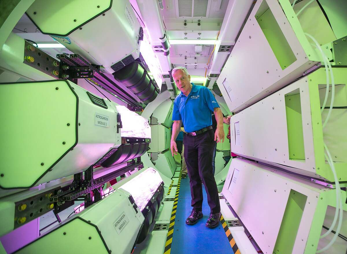 Former NASA astronaut, space shuttle commander and current Sierra Nevada Corporation (SNC) vice president Steve Lindsey leads a tour of SNC's prototype for an inflatable space habitat that could be used for NASA's lunar orbital platform gateway project, during a press event at Johnson Space Center in Houston, Wednesday, Aug. 21, 2019. The purple glow comes from a vegetable growing system on display that SNC designed and is currently operating on the International Space Station. The habitat is designed to fit inside the cargo area of a commercial launch vehicle and then be inflated and outfitted in space. The habitat as currently modeled consists of three floors outfitted for a crew of four astronauts.