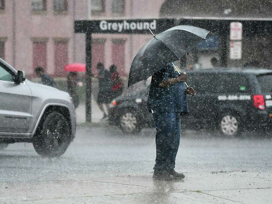 A man stands near the Greyhound bus station with an umbrella during a thunderstorm on Wednesday, Aug. 21, 2019 in Albany, N.Y. (Lori Van Buren/Times Union) Photo: Lori Van Buren, Albany Times Union