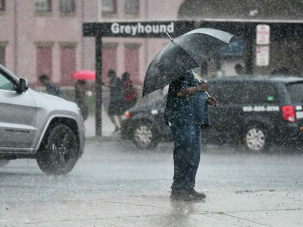 A man stands near the Greyhound bus station with an umbrella during a thunderstorm on Wednesday, Aug. 21, 2019 in Albany, N.Y. (Lori Van Buren/Times Union)