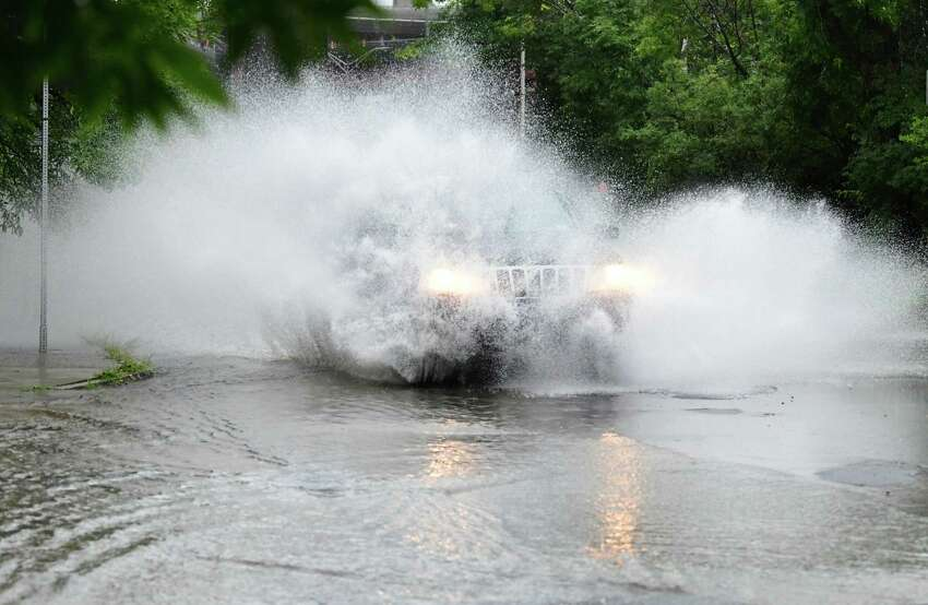 A car rushes through a water on Madison Ave. on Wednesday, Aug. 21, 2019 in Albany, N.Y. A heavy rain during a thunderstorm caused the bottom of Madison Avenue to partially flood. (Lori Van Buren/Times Union)