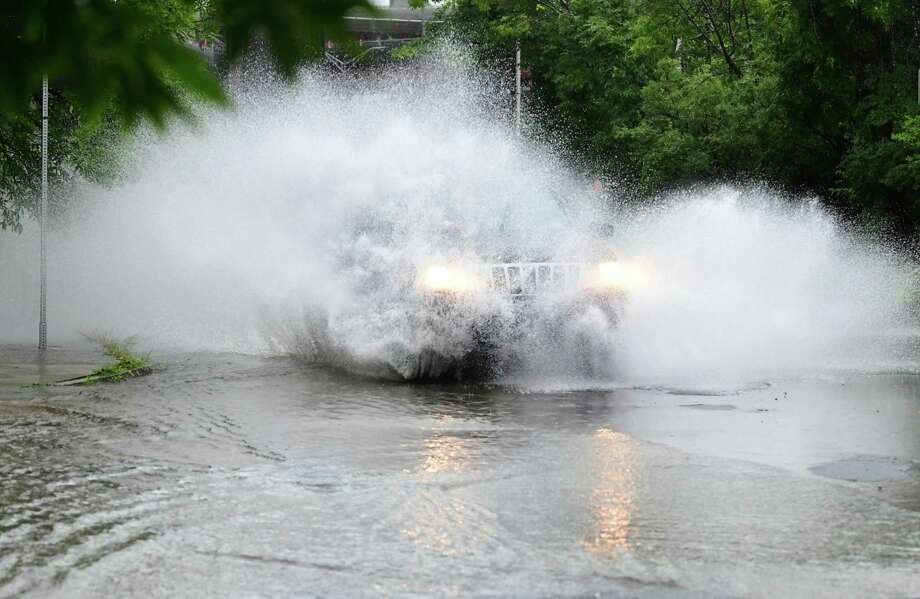 A car rushes through a water on Madison Ave. on Wednesday, Aug. 21, 2019 in Albany, N.Y. A heavy rain during a thunderstorm caused the bottom of Madison Avenue to partially flood. (Lori Van Buren/Times Union) Photo: Lori Van Buren, Albany Times Union
