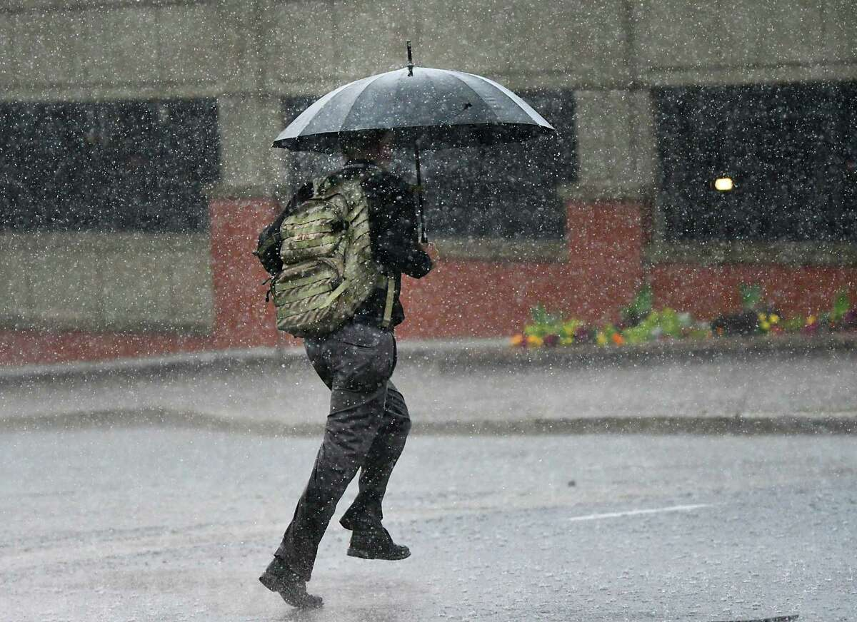 A man makes runs down Madison Ave. with an umbrella during a thunderstorm on Wednesday, Aug. 21, 2019 in Albany, N.Y. The National Weather Service issued a tornado watch Aug. 2, 2020 with the possibility of localized strong thunderstorms. (Lori Van Buren/Times Union)