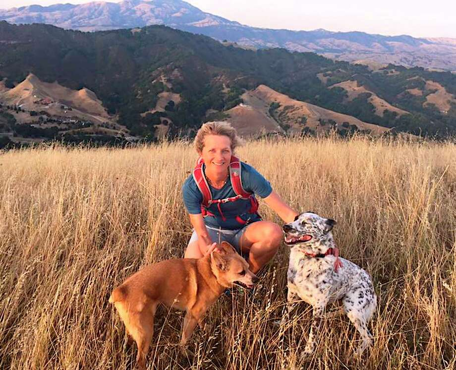 Shelly Lewis and her dogs Lucky and Taz on the trail of her favorite hike, to Rocky Ridge at Las Trampas Regional Wilderness Photo: Lance Lewis