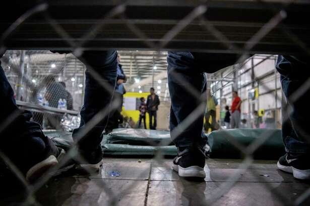 Men sit on a bench with other fathers of young children in the U.S. Border Patrol Central Processing Center in McAllen, Texas, on Aug. 12. Border Patrol officials said that 1,267 people were being held and processed in the facility at the time of the tour.