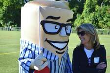 Cindi Bigelow, president and CEO of Bigelow Tea chats with Biggie the event mascot at the 29th annual Bigelow Tea Community Challenge, Sunday, Sept. 25, 2016, in Fairfield, Conn.