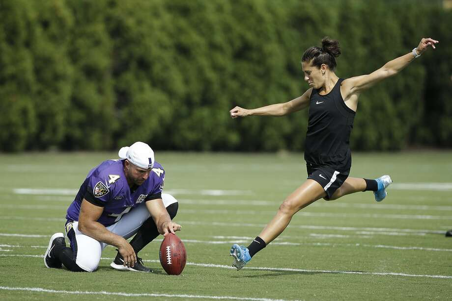 Baltimore Ravens' Sam Koch holds the ball for United States soccer player Carli Lloyd as she attempts to kick a field goal after the Philadelphia Eagles and the Baltimore Ravens held a joint NFL football practice in Philadelphia, Tuesday, Aug. 20, 2019. (AP Photo/Matt Rourke) Photo: Matt Rourke, Associated Press