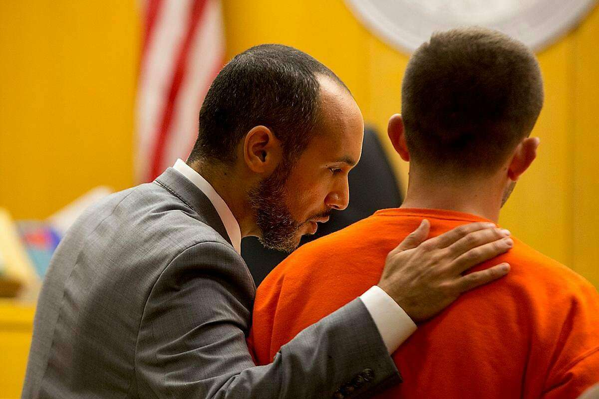 Deputy Public Defender Saleem Belbahri places his hand on his client, Austin James Vincent, a suspect in a highly-publicized attack outside a condo building near the Embarcadero, during his court appearance at the Hall of Justice on Tuesday, Aug. 20, 2019. (Kevin N. Hume/S.F. Examiner)