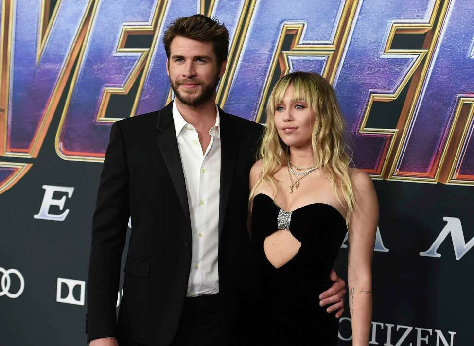 FILE - In this Monday, April 22, 2019, file photo, Liam Hemsworth, left, and Miley Cyrus arrive at the premiere of