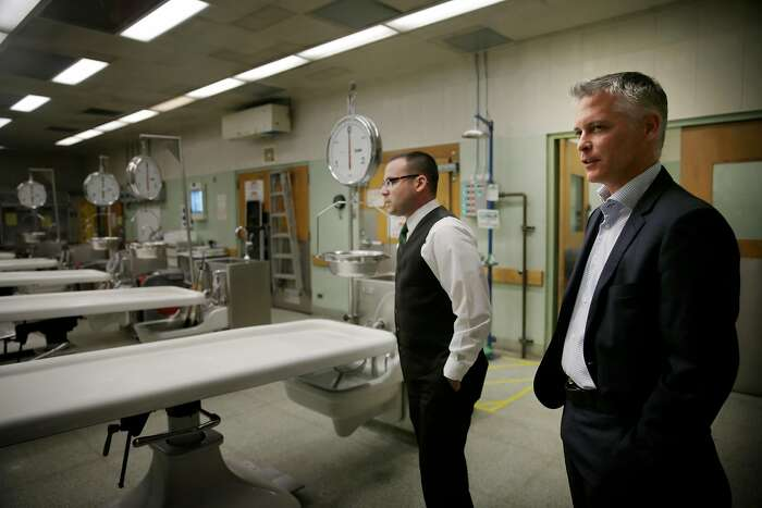 San Francisco Chief Medical Examiner Michael Hunter (right) and Christopher Wirowek (left), deputy director Medical Examiner's Office, talk as they stand in the autopsy suite during a tour at the Hall of Justice on Wednesday, November 18, 2015 in San Francisco, Calif.