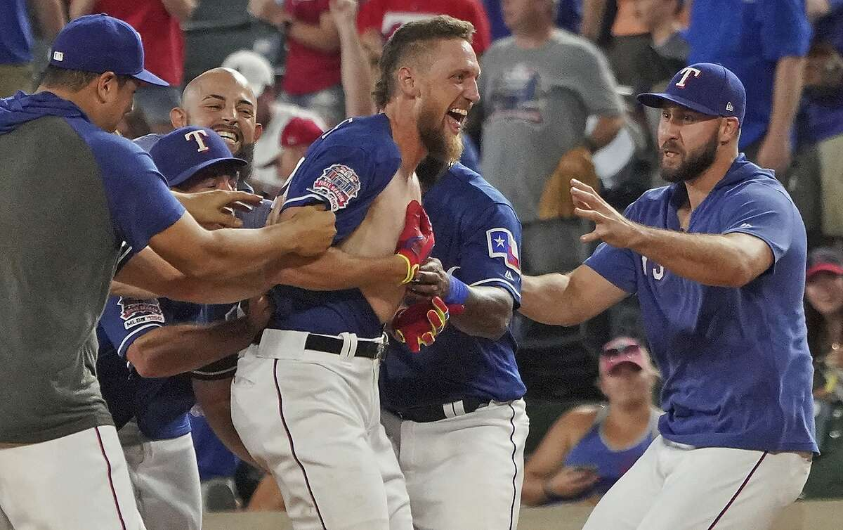 Texas Rangers' Hunter Pence is mobbed by teammates after driving in the winning run against the Los Angeles Angels during the ninth inning of a baseball game Wednesday, Aug. 21, 2019, in Arlington, Texas. The Rangers won 8-7. (AP Photo/Louis DeLuca)
