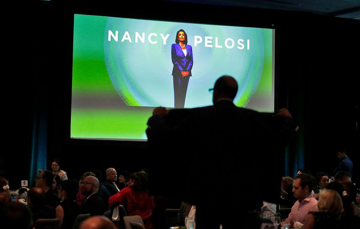 Protester holds a sign in the audience as Nancy Pelosi received a lifetime achievement award from the San Francisco Democratic Party at the Intercontinental Hotel in San Francisco, Calif., on Wednesday, August 21, 2019. There were a large number of groups picketing outside and several protesters managed to get into the event to urge her to launch impeachment proceedings.