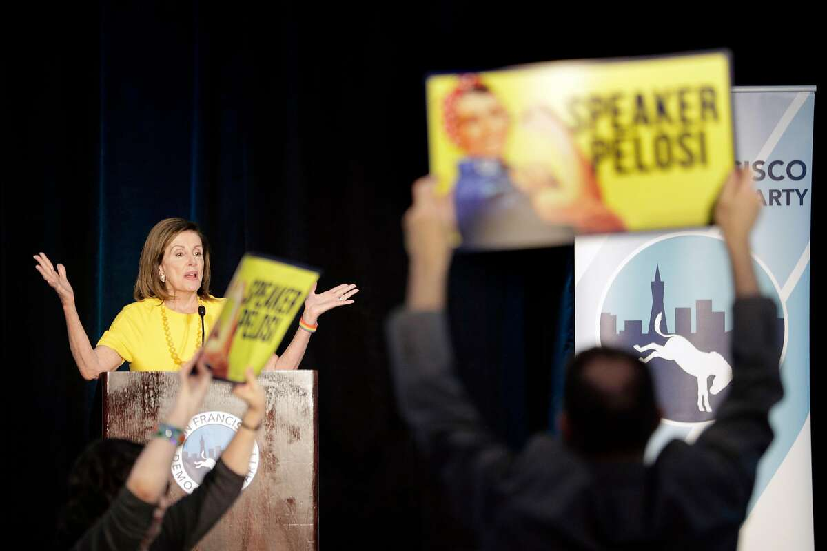 Supporters hold up signs as protesters yell at Speaker Nancy Pelosi after she received a lifetime achievement award from the San Francisco Democratic Party at the Intercontinental Hotel in San Francisco, Calif., on Wednesday, August 21, 2019. There were a large number of groups picketing outside and several protesters managed to get into the event to urge her to launch impeachment proceedings.