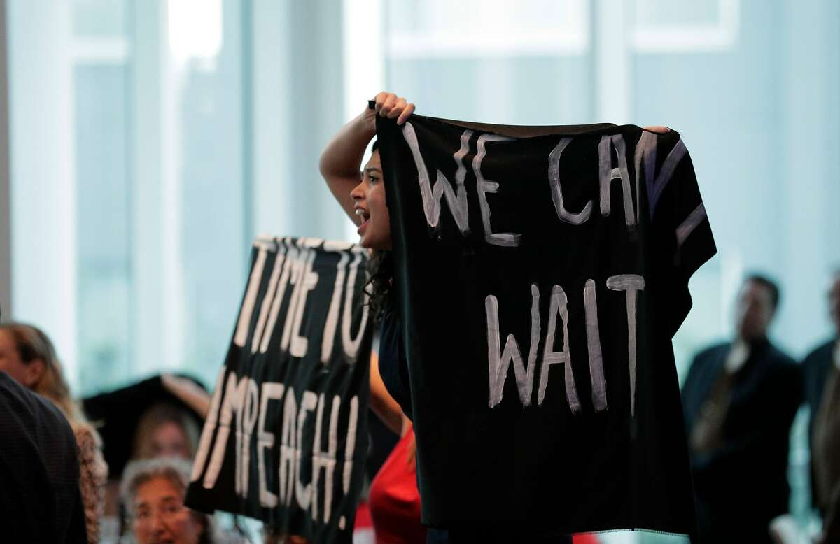 """Thais Marques, front, and Karen Fleshman, rear. with Credo, yell and holds banner reading, """"We Can't Wait,"""" and """"Time To Impeach!"""" as Nancy Pelosi received a lifetime achievement award from the San Francisco Democratic Party at the Intercontinental Hotel in San Francisco, Calif., on Wednesday, August 21, 2019. There were a large number of groups picketing outside and several protesters managed to get into the event to urge her to launch impeachment proceedings."""