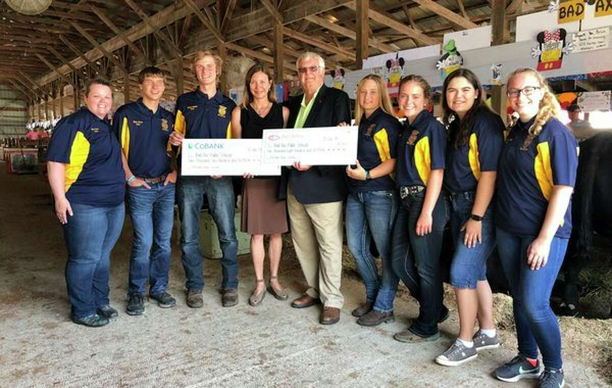 Jacqueline Bove of CoBank and Edwin H. Eichler of Agri-Valley Communications (center) present checks totaling $8,000 to Bad Axe Public Schools teacher and FFA advisor Victoria Yackle (far left), along with her FFA students. The funds will provide a remote video surveillance system for the district's new FFA and Agri-Science Livestock Barn. (Submitted Photo)