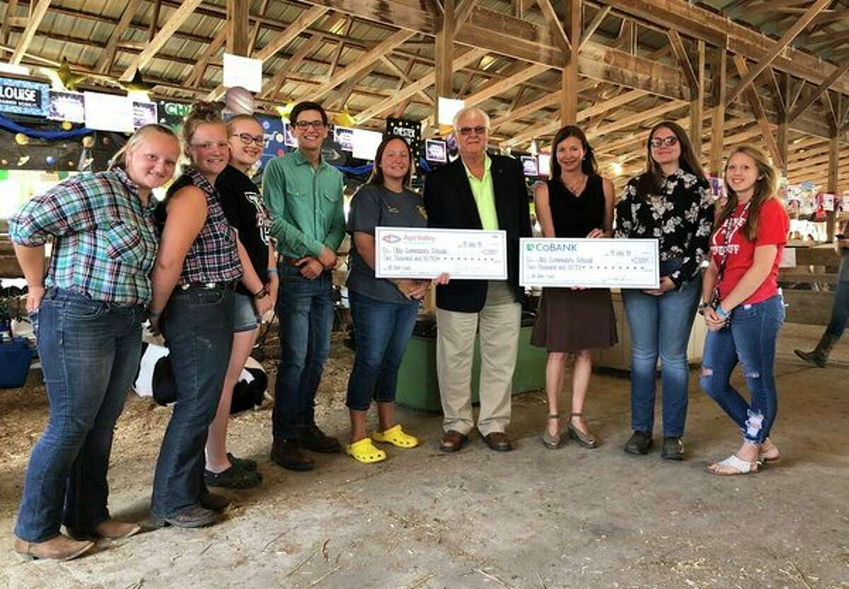 Edwin H. Eichler of Agri-Valley Communications and Jacqueline Bove of CoBank (fourth and third right) present checks totaling $4,000 to Ubly Community Schools teacher and FFA advisor Melissa Kramer (center) and her FFA students. The funds will assist in the construction of the district's new FFA barn.