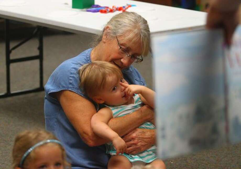 Hazel Leak sits with her grandmother Judy Leak during story time Wednesday at Jacksonville Public Library. Photo: Rosalind Essig | Journal-Courier