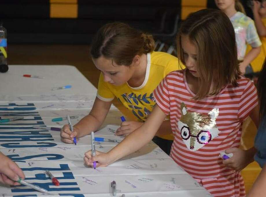 Vivian Thomas (left), a fourth grader, and Ivana Thomas, a second grader, sign a banner showing their intent to take on Rachel's Challenge to be a kinder person. Photo: Samantha McDaniel-Ogletree | Journal-Courier