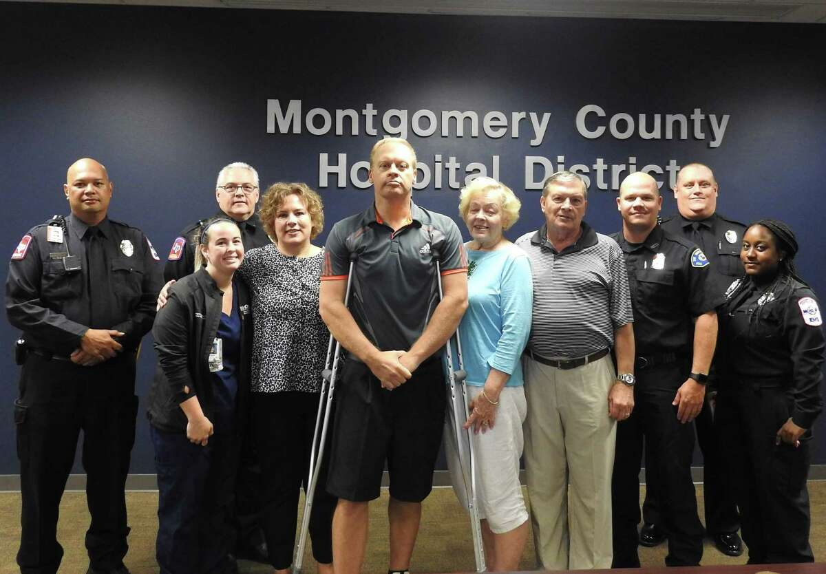 Tom Dreier stand at center surrounded by family and Montgomery County Hospital District personnel who helped save his life after he suffered a cardiac arrest while driving in The Woodlands.