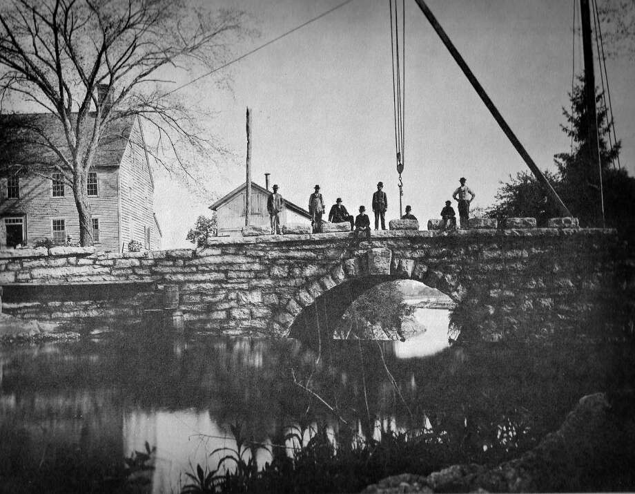 The building of Memorial Bridge, 1888-1889, by John Beatty of Leetes Island. The granite blocks that have the names of the first settlers are being set on the north coping with the aid of a hand-operated crane. The building to the left is the Fowler Homestead. Photo: Photo From Daniel And Roma Moger Collection.