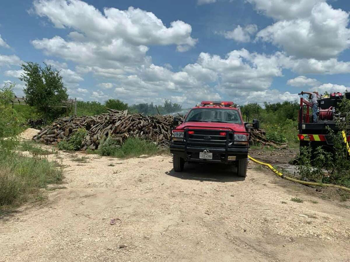 Firefighters from the York Creek Volunteer Fire Department douse a brush pile near Martindale that had begun to burn.