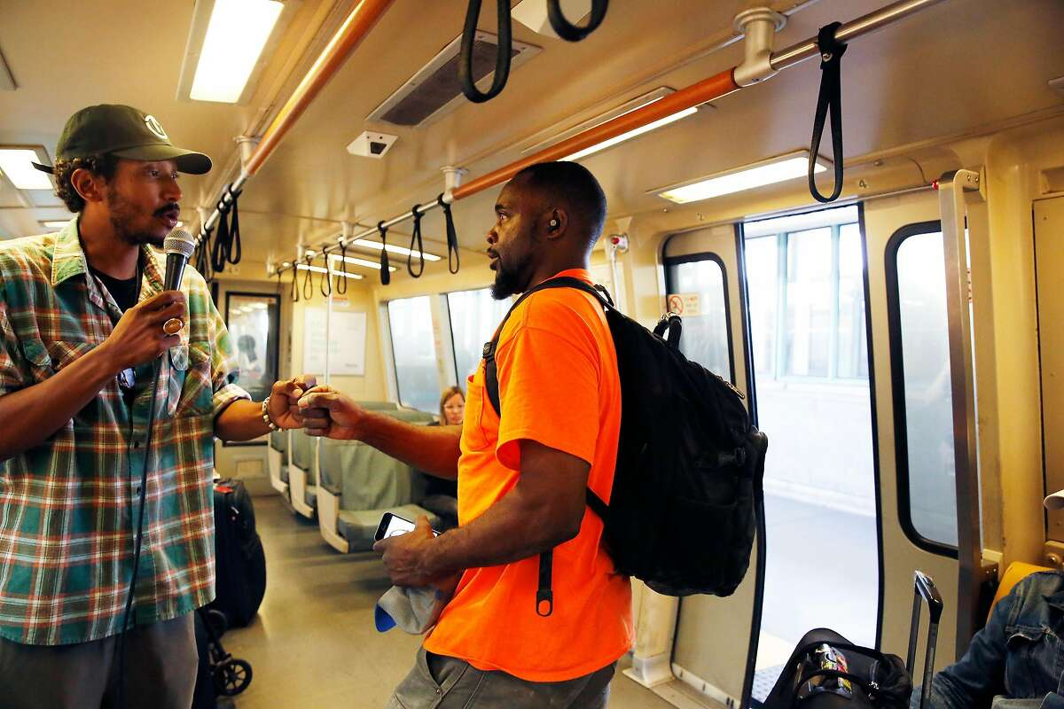 Tone Oliver (l to r) fist bumps with Leonard Haulcy of Oakland as Haulcy departs from the train after donating into Oliver's container as Oliver performs on a BART train for passengers on Wednesday, August 14, 2019 in Oakland, Calif.