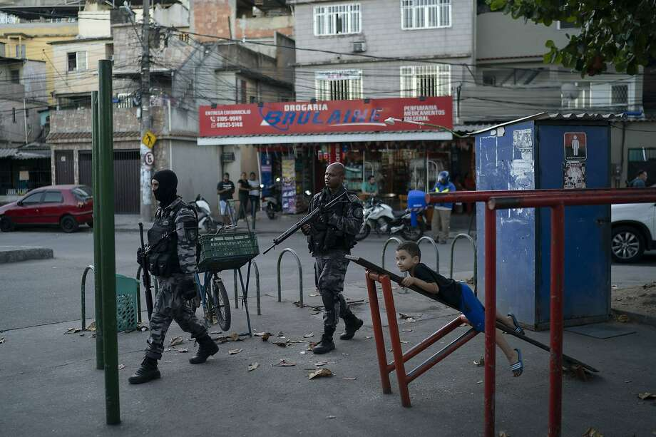 Police officers patrol the Mare slum in Rio de Janeiro. The 194 deaths reported by state officials for July was the most killings involving police in a single month since at least 1998. Photo: Leo Correa / Associated Press