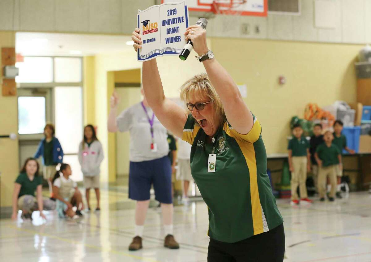 Physical Education teacher Mary Westfall reacts after learning she was awarded a grant as the San Antonio Independent School District Foundation surprises teachers at Bonham Academy on Thursday. ,Educators applied for the grants in the spring. They range from $1,000 to $5,000 for each of the 56 winners this year, totaling more than $200,000. (Kin Man Hui/San Antonio Express-News)
