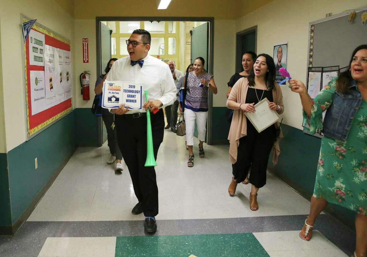 Principal David Nungaray (center) leads the way to award educators with grants from the San Antonio Independent School District Foundation at Bonham Academy on Thursday. Educators applied for the grants in the spring. They range from $1,000 to $5,000 for each of the 56 winners this year, totaling more than $200,000. (Kin Man Hui/San Antonio Express-News)