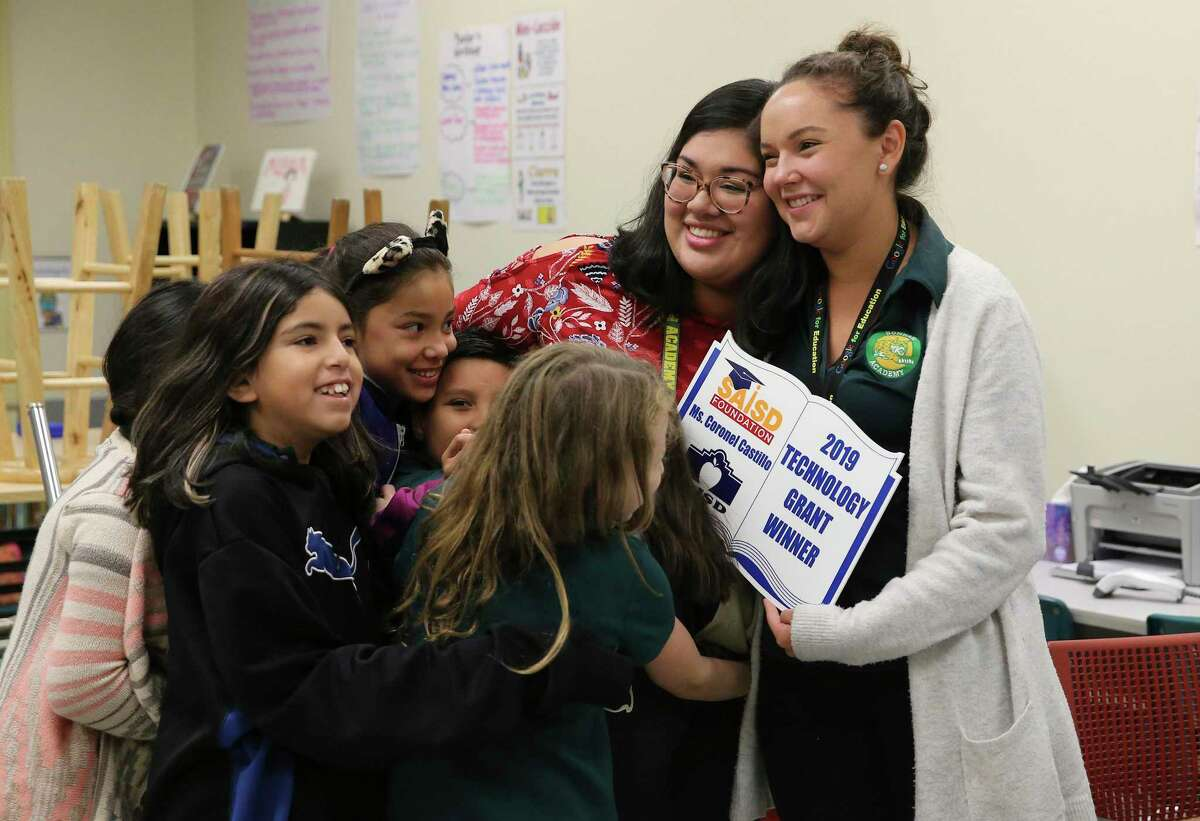Students prepare to hug Daritza Coronel Castillo (center) as she and fellow fourth-grade teacher Iliana Storch (right) learn Thursday that they were awarded a grant from the San Antonio Independent School District Foundation to fund educational projects. Educators applied for the grants in the spring. They range from $1,000 to $5,000 for each of the 56 winners this year, totaling more than $200,000. (Kin Man Hui/San Antonio Express-News)