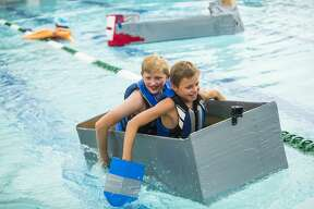 Matthew McGaugh, 11, front, and James Glackin, 13, back, race their boat across the swimming pool at the Midland Country Club during a cardboard regatta on Tuesday, Aug. 20, 2019. (Katy Kildee/kkildee@mdn.net)
