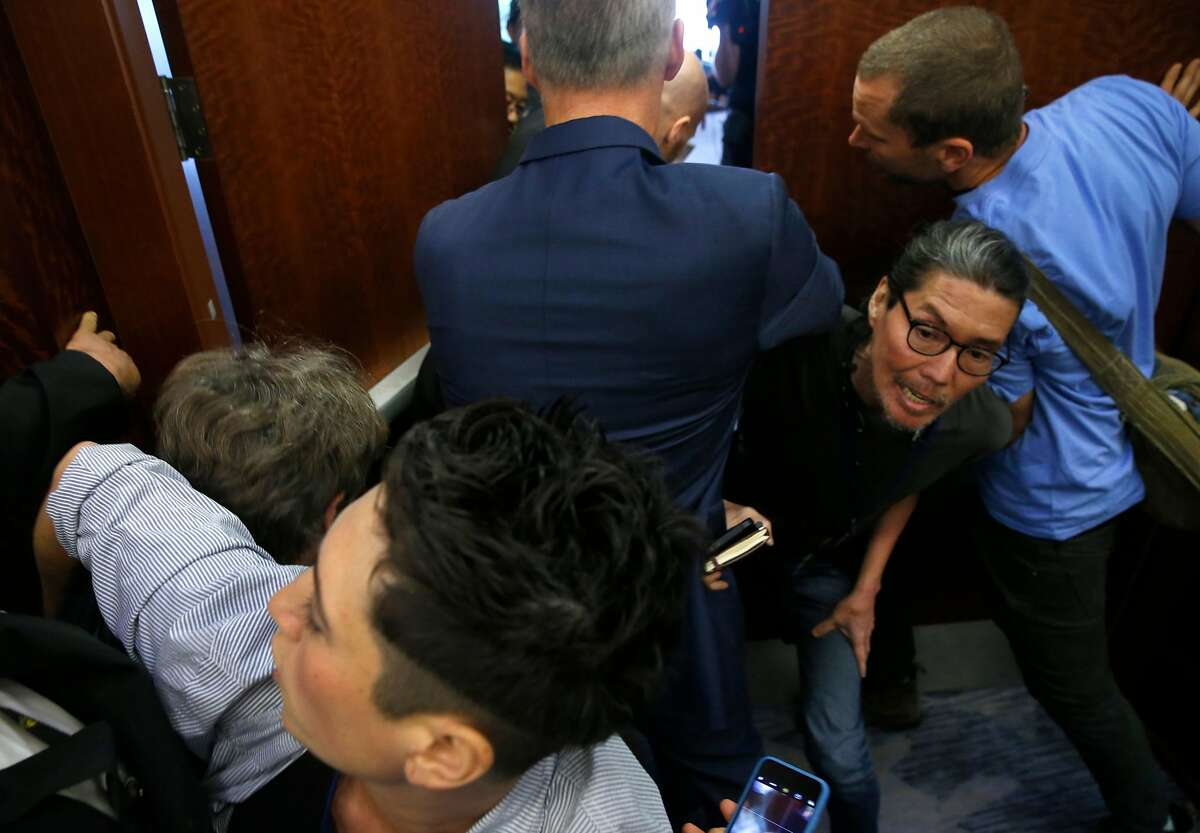 Protesters supporting a presidential candidate debate on climate change struggle to get past security guards during a meeting of the Resolutions Committee at the DNC summer meeting at the Hilton Hotel in San Francisco, Calif. on Thursday, Aug. 22, 2019. The group was eventually allowed inside.