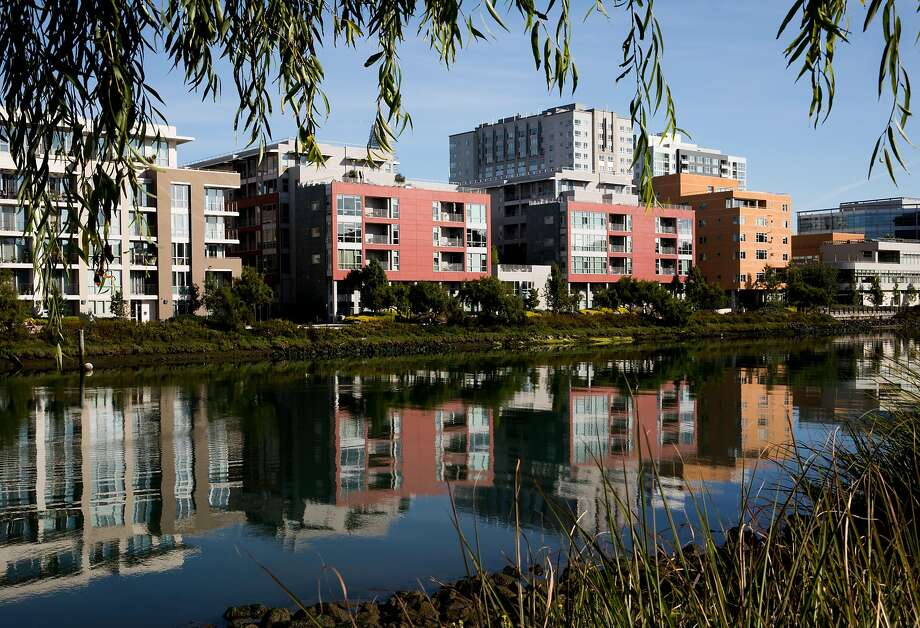 New apartments and office buildings are seen reflected in the waters of Mission Creek, which is home to the only longtime residents of the Mission Bay neighborhood, a community living aboard 20 houseboats moored in the creek. Photo: Jessica Christian / The Chronicle