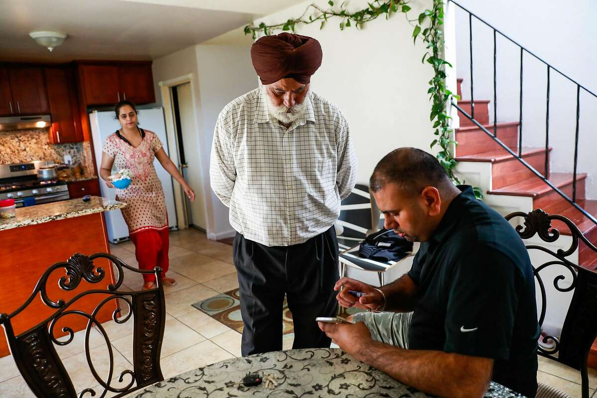 Taxicab driver Jeet Ghotra (center) chats with his son Gagandip Singh at his home in South San Francisco, California, on Wednesday, Aug. 21, 2019. At 68, Jeet wants to retire but he can't because he took out a second mortgage on his South San Francisco home to buy a $250,000 taxi medallion.