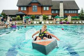 Drew Dittenber, 9, races his boat across the swimming pool at the Midland Country Club during a cardboard regatta Tuesday. For more photos, visit www.ourmidland.com. (Katy Kildee/kkildee@mdn.net)