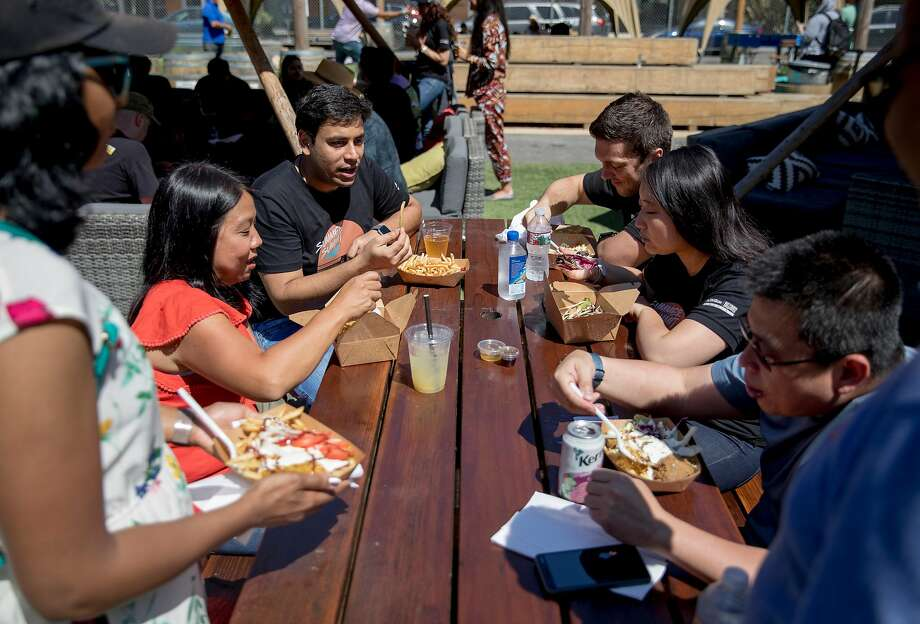 A group of co-workers enjoy lunch from various food trucks at Parklab Gardens sponsored by Spark Social SF in the Mission Bay neighborhood of San Francisco, Calif. Thursday, August 22, 2019. Photo: Jessica Christian / The Chronicle