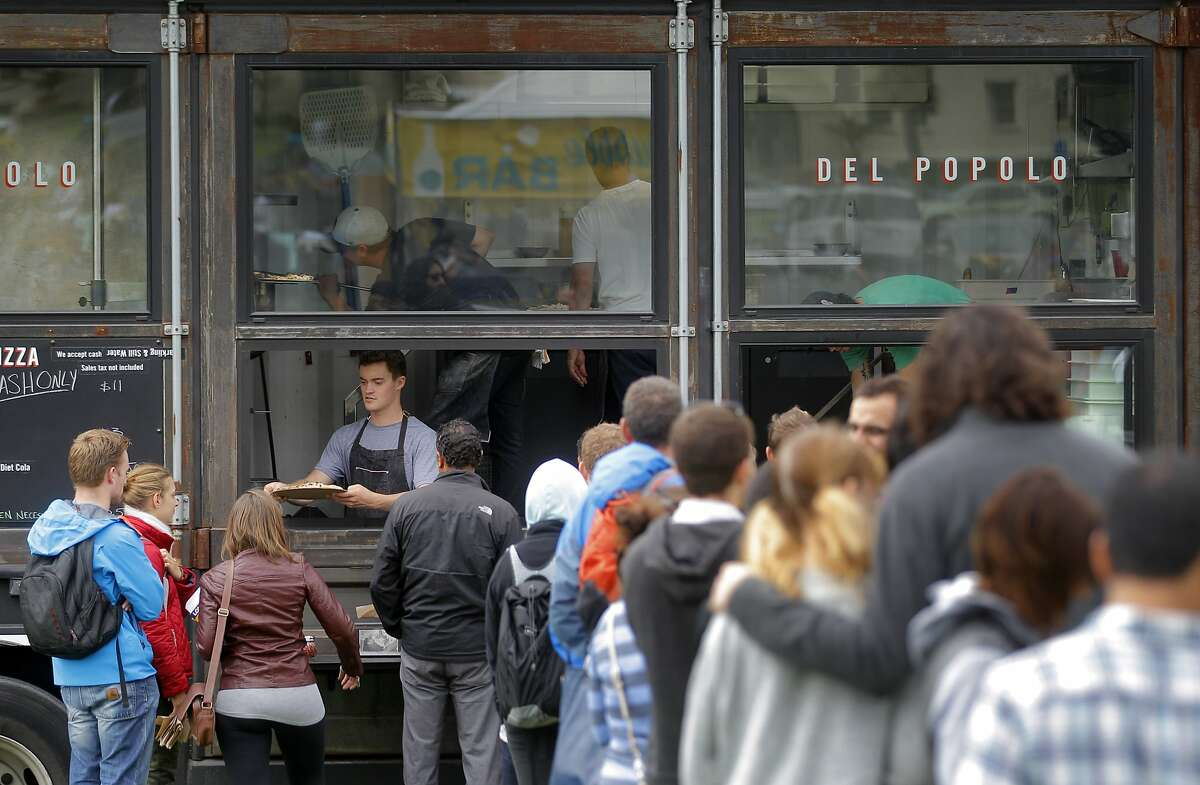 People line up at the Del Popolo Pizza food truck during Off the Grid's Presidio Picnic event in 2014. The popular Sunday market will remain closed until at least the fall.