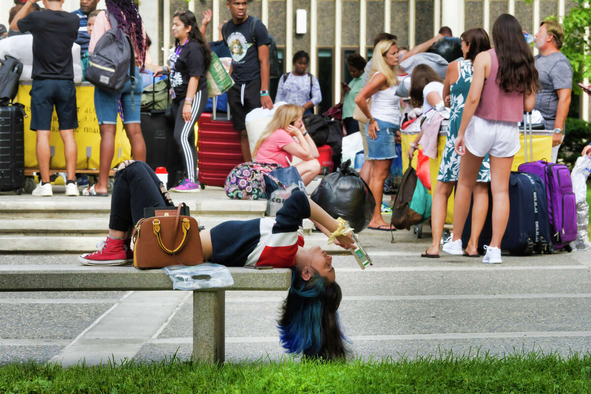 University at Albany freshman Franki Salazar from Whittier, CA reads a book on a bench as fellow freshman students along with their family members wait in line outside one of the dorm towers during move-in day on Thursday, Aug. 22, 2019, in Albany, N.Y. Salazar had already moved into her dorm room and was just relaxing with a book. (Paul Buckowski/Times Union)