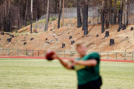 Quarterback Danny Bettencourt passes near the stumps from fire-damaged trees during practice. Photo: Scott Strazzante / The Chronicle