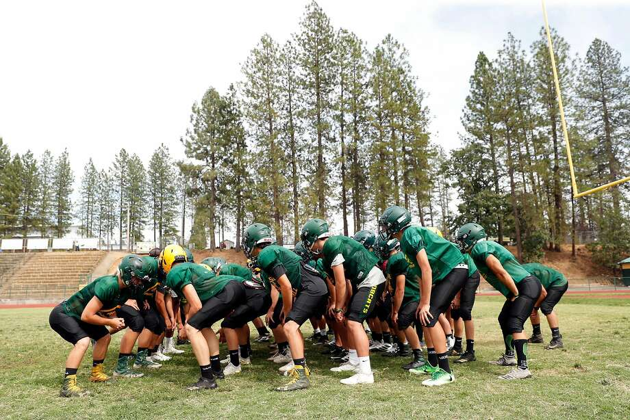 Team members huddle up at start of varsity football practice at Paradise High School in Paradise, Calif., on Wednesday, August 21, 2019. Photo: Scott Strazzante / The Chronicle