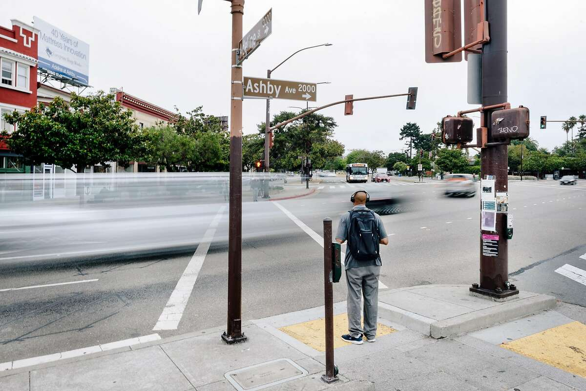 Traffic passes by as a pedestrian waits to cross Ashby Avenue at Adeline Street in Berkeley. State Sen. Scott Wiener is pressing a bill to make Caltrans consider improvements for bicycles and pedestrians whenever it starts a major street project on a state highway that actually functions as a city street, such as Ashby Avenue in Berkeley.
