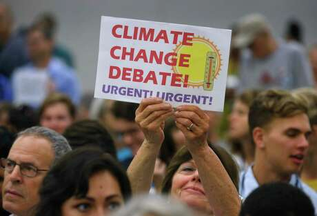 An audience member holds up a sign calling for a debate on climate during a meeting of the Resolutions Committee at the DNC summer meeting at the Hilton Hotel in San Francisco, Calif. on Thursday, Aug. 22, 2019.