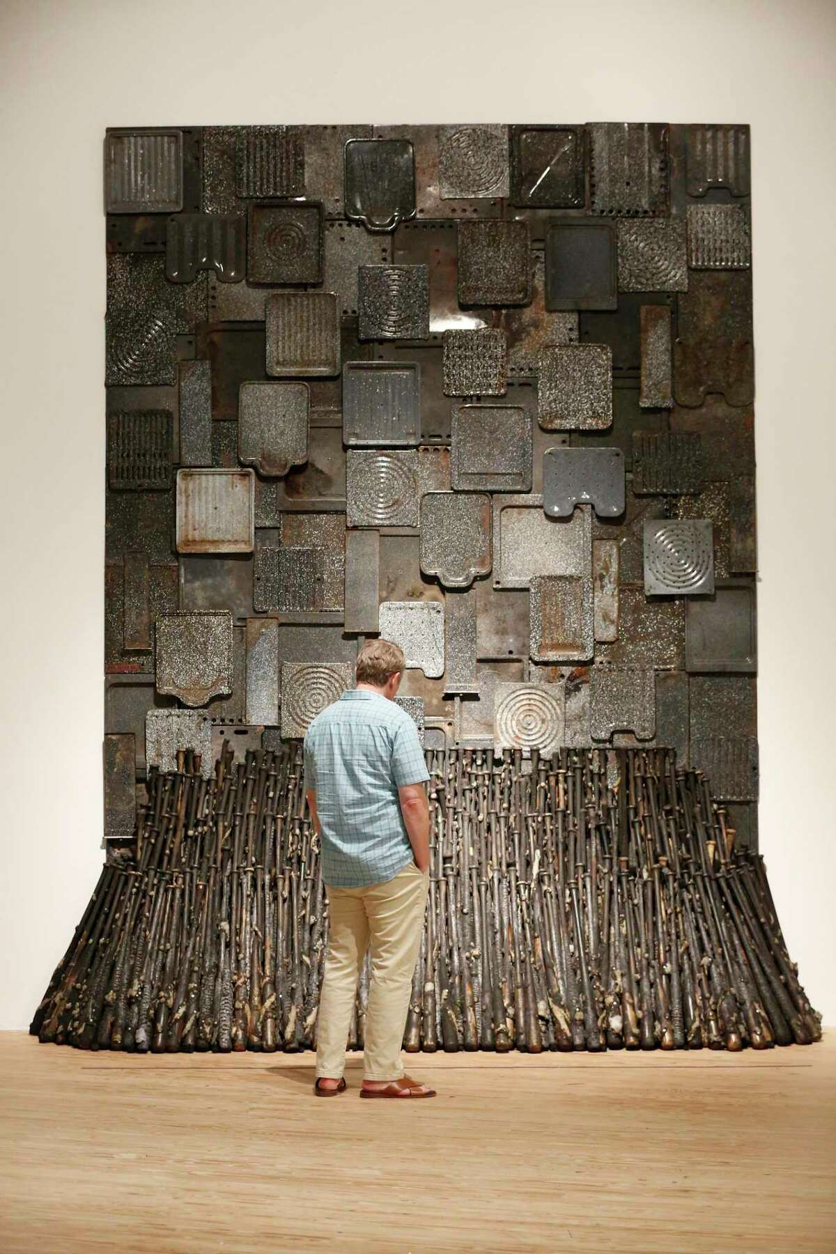 """A visitor looks at Nari Ward: """"We the People"""" Iron Heavens at the Contemporary Arts Museum Houston part of a 25-year survey of large-scale sculptures Wednesday, Aug. 21, 2019, in Houston."""