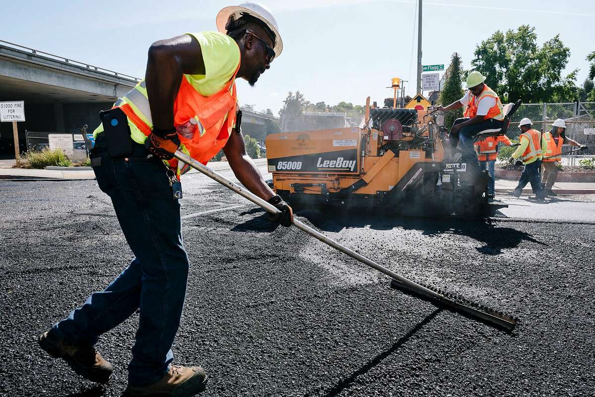 Oakland Department of Transportation worker James Akinjo rakes and smooths asphalt as crews paves Harold St. in Oakland, Calif., on Thursday, August 22, 2019. Oakland Mayor Libby Schaaf and city council member Noel Gallo announced the launch of a $100 million paving program, which over the next three years will address some of the most underserved communities whose streets have been neglected for years.